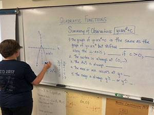 A senior years student does math on a whiteboard
